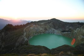 Sunrise behind the turquoise lake at Kelimutu